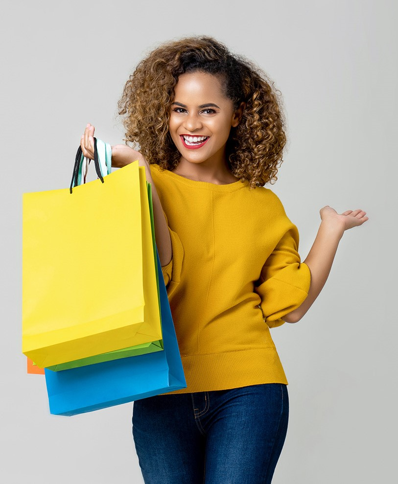 Young lady smiling and holding colorful shopping bags